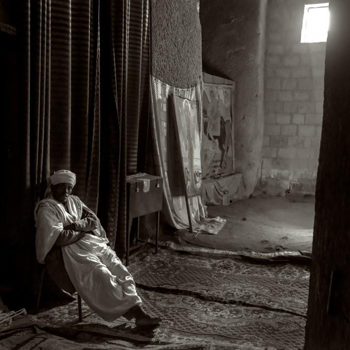 foto in bianco e nero, prete a riposare in chiesa