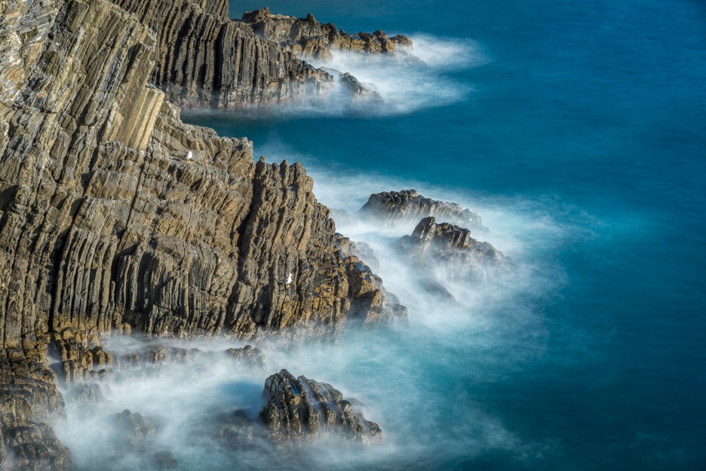 lunga esposizione di onde sulle rocce a riomaggiore