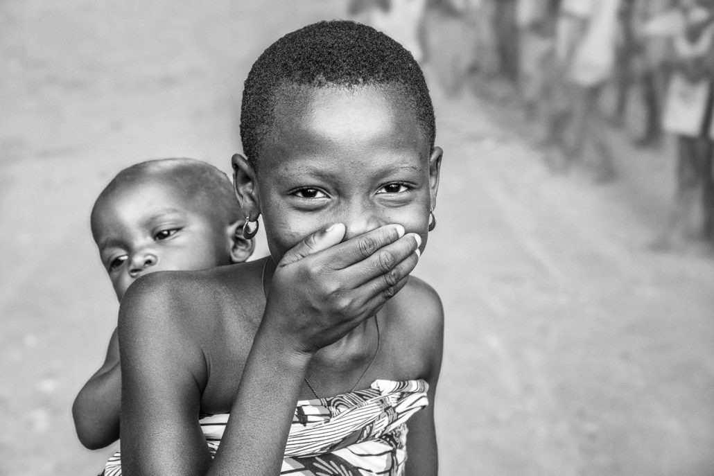 Girl in Benin, taking care of her little sibling, black and white