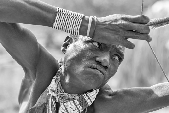 a Hadzabe hunter aiming with bow and arrow, Tanzania, Lake Eyasi