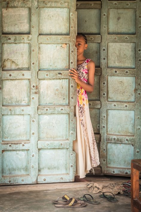 Tanzania, Pangani. A girl in a doorway of a colonial building