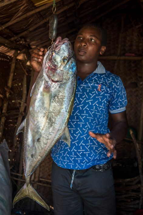 a young fishermen on the island songo Mnara weighing his fish for sale