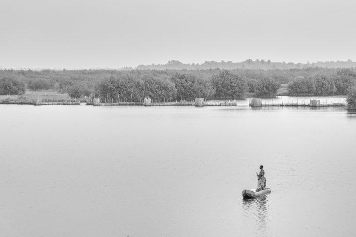 woman on her canoe in the lagoon of Ouidah