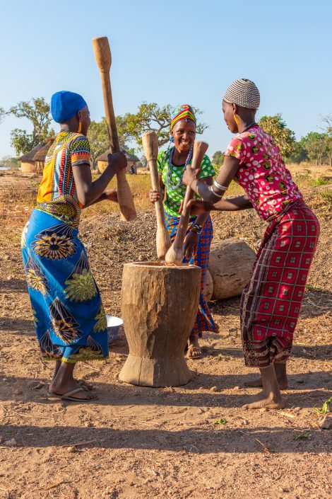 Fulani village, girls pounding cereals with a mortar